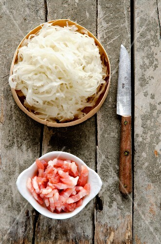 Fresh sauerkraut from Alsace in a wooden dish, lardons of bacon and a rustic knife