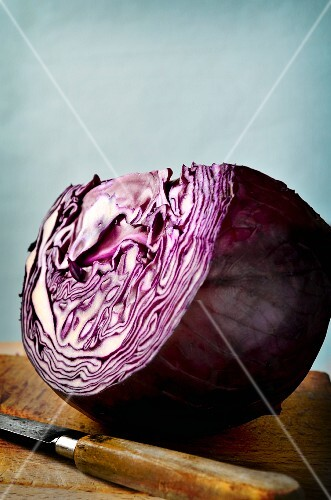 A large wedge of red cabbage on a wooden board with a knife