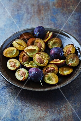 whole and halved plums on a ceramic plate