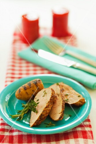 Slices of roast pork with grilled potatoes, rosemary and thyme