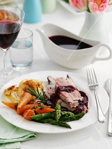 Sliced roast leg of lamb with vegetables