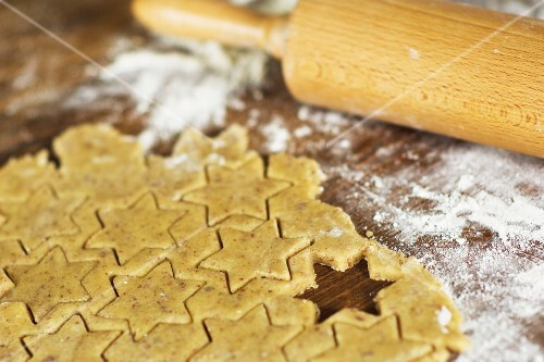 Cut-out almond biscuits, flour and a rolling pin