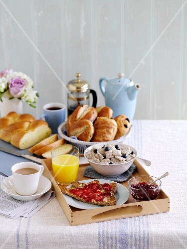 A breakfast tray with toast, cereals, jam, sweet bread, coffee and tea