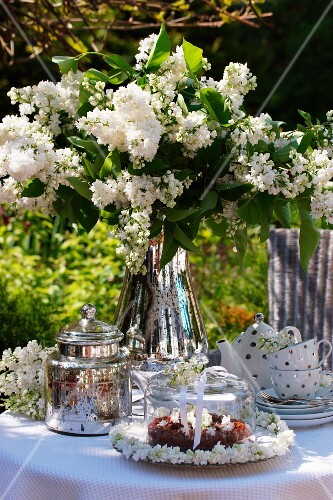 Chocolate cake, a tea set and white lilacs on a garden table