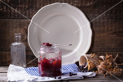 Jar of plum and juniper jam on old wooden background