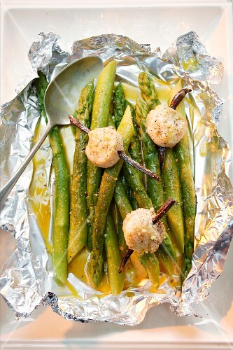Green asparagus with scallops in aluminium foil