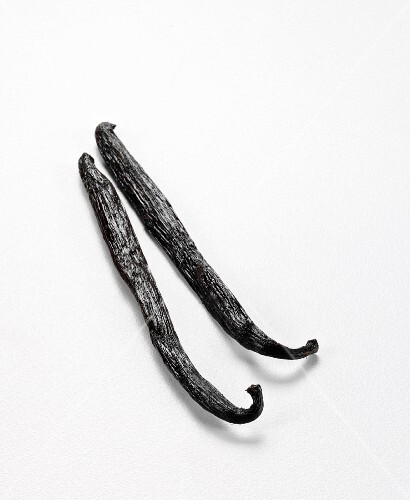 Two vanilla pods against a white background