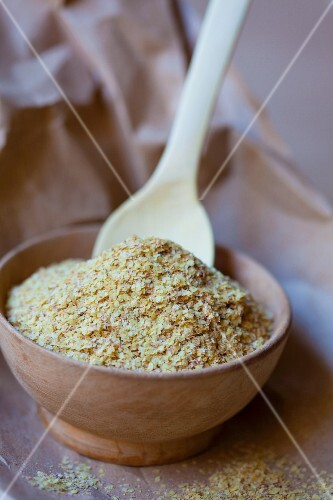 Wheat germ in a wooden bowl with a spoon