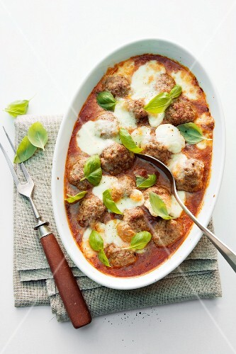 Baked meatballs in tomato sauce with mozzarella and basil