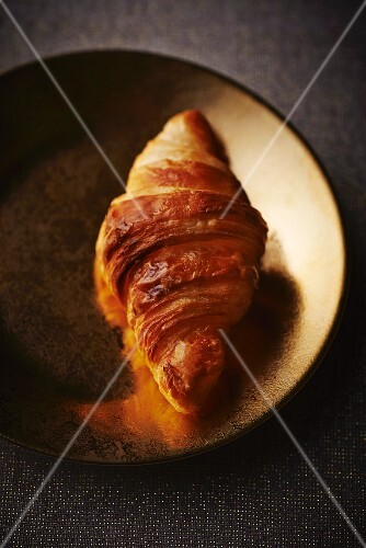 Croissant on a gold plate