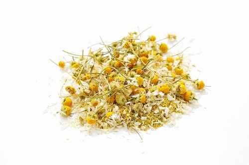 Dried camomile leaves against a white background