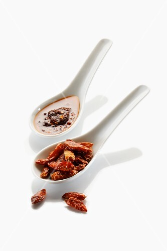 Two spoons with dried chillies and chilli oil