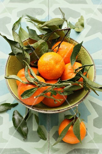 Mandarins with water droplets and leaves in a bowl