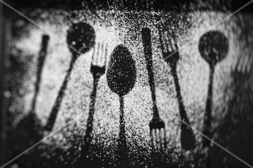 The outlines of forks and spoons in icing sugar on a dark surface