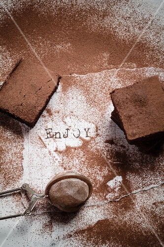 Three brownies dusted with cocoa on a scrap of white paper with the word Enjoy