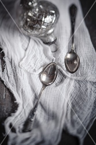 Two teaspoons and a silver Christmas bauble on a muslin cloth