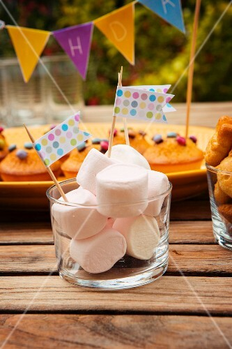 Marshmallows decorated with flags and muffins with chocolate beans for a child's birthday
