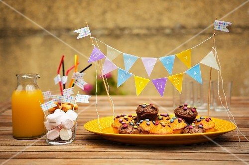 Muffins with chocolate beans, marshmallows and orange juice for a child's birthday