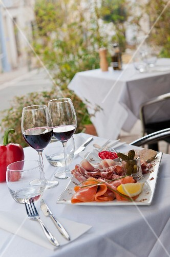 Antipasti platter and glasses of red wine on a restaurant table outdoors (Italy)