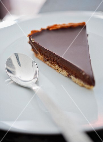 A slice of chocolate tart on a plate with a spoon