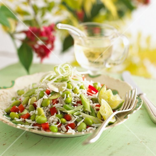 Rice salad with soy beans and lime wedges