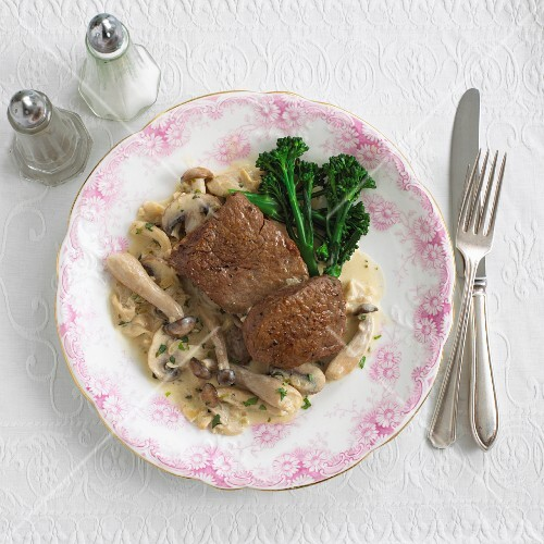 Four Filet Mignon Steaks on a Plate, Three Topped with Mushroom Sauce