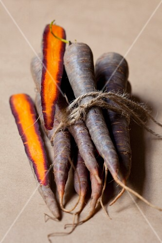 Several purple carrots tied in a bunch