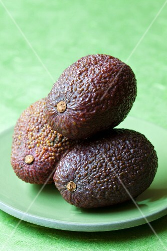 Three avocados on a green plate