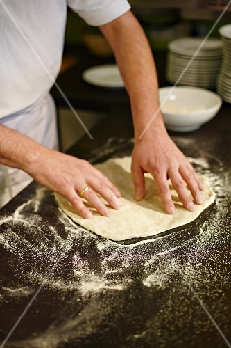 Pizza dough being stretched