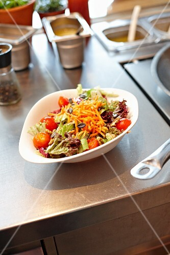 Salad leaves with carrots and tomatoes in a restaurant kitchen