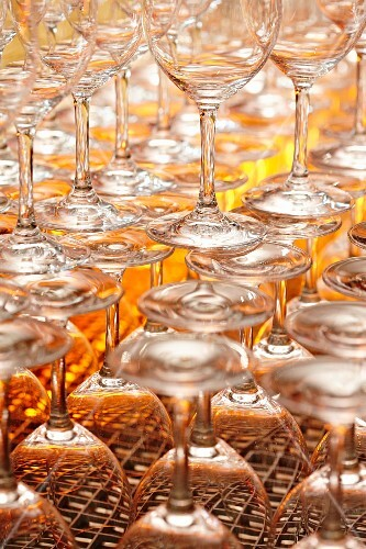 Several rows of empty, clean wine glasses in a restaurant