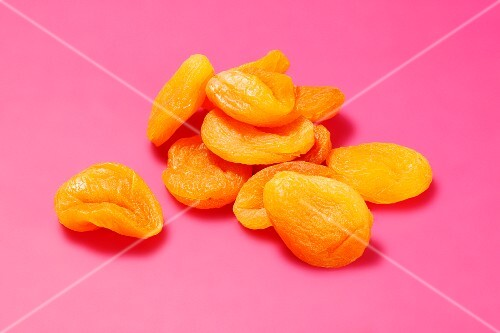 Dried apricots on a bright pink surface