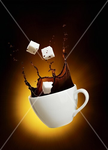 A splash of coffee with sugar cubes