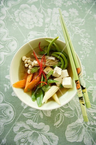 Asian vegetable soup with tofu and enoki mushrooms