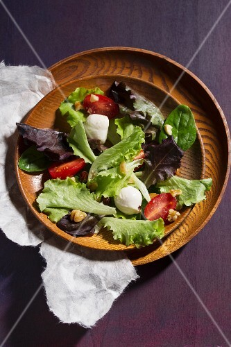 Mixed salad with mozzarella, tomatoes and walnut pieces in a wooden bowl
