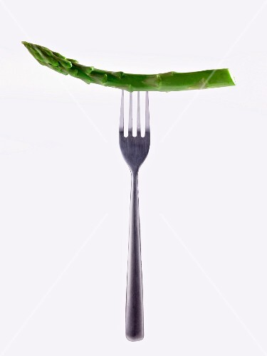 A stem of green asparagus on a fork