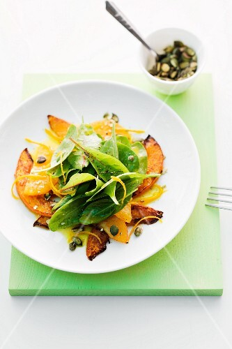 Spinach salad with squash, orange and pumpkin seeds