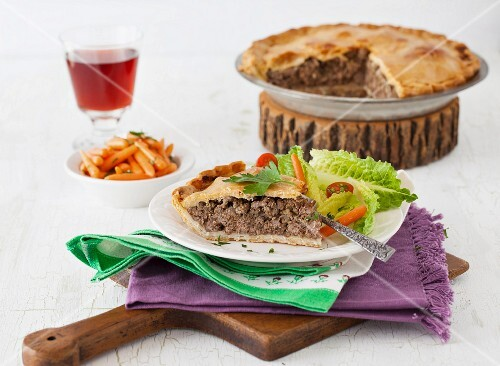 Slice of Traditional Tourtière - Canadian Meat Pie with greens and carrots