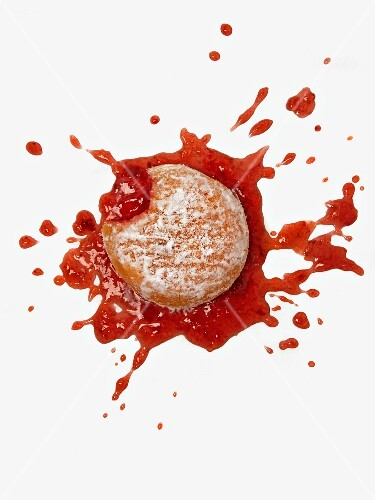 A dropped doughnut; jam has squirted out in all directions