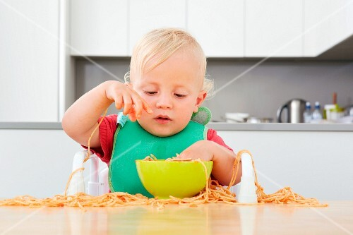 A small child playing with spaghetti