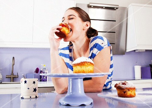 A woman biting into a muffin, with great enjoyment