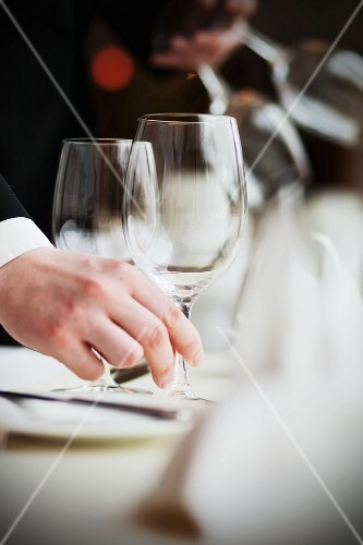 A waiter placing an empty wine glass on a table in a restaurant