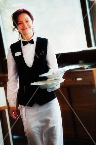 A waitress carrying two bowls of soup
