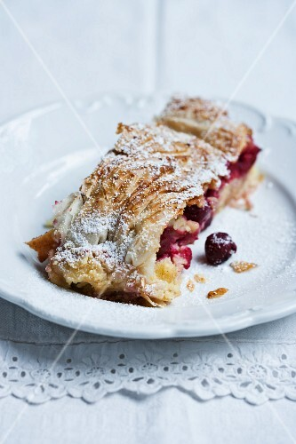 A slice of cherry strudel with icing sugar