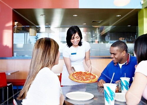 Teenagers being served pizza at restaurant