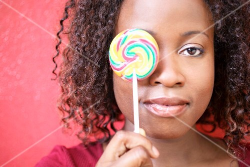 Woman holding lollipop in front of her eye