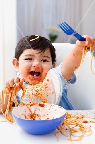 Baby boy in high chair laughing spaghetti mess