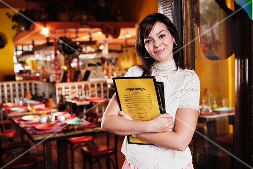 Portrait of hostess with menus in restaurant