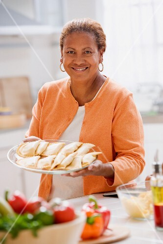 Woman holding out a plate of dumplings