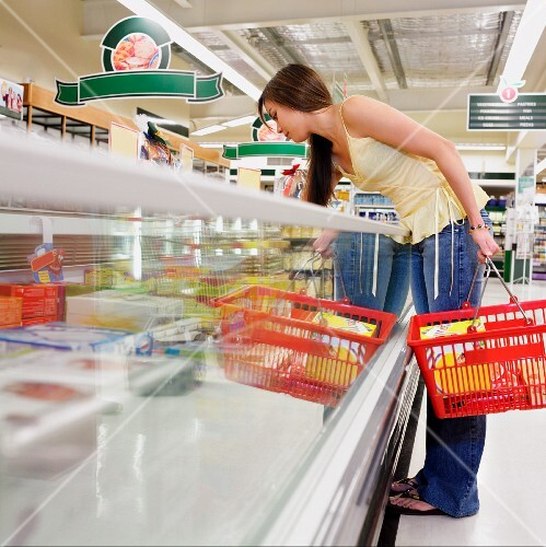 Woman selecting frozen food at supermarket